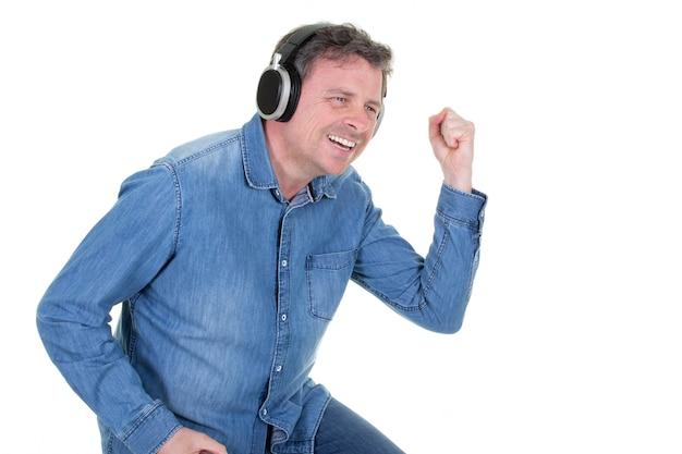 Bel homme vêtu d'une chemise bleue est debout avec un sourire joyeux et danse avec ses yeux fermés