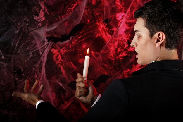 Bel homme vêtu d'un costume de dracula pour halloween. vampire attrayant avec des bougies