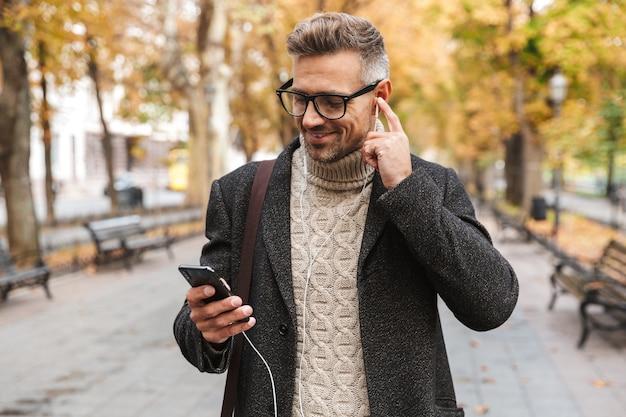 Bel homme vêtu d'un manteau marchant à l'extérieur, écoutant de la musique avec des écouteurs et un téléphone mobile