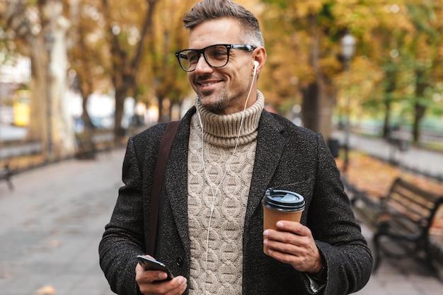 Bel homme vêtu d'un manteau marchant à l'extérieur, écoutant de la musique avec des écouteurs et un téléphone portable, tenant une tasse de café à emporter