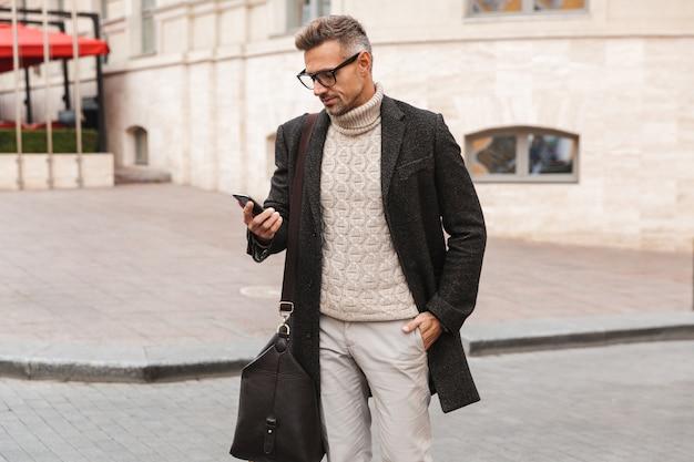 Bel homme vêtu d'un manteau marchant à l'extérieur, tenant un téléphone mobile