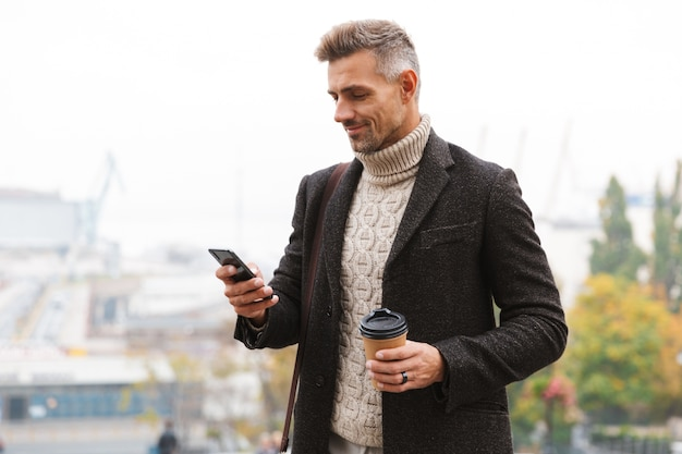 Bel homme vêtu d'une veste marchant à l'extérieur, tenant une tasse de café à emporter, utilisant un téléphone mobile