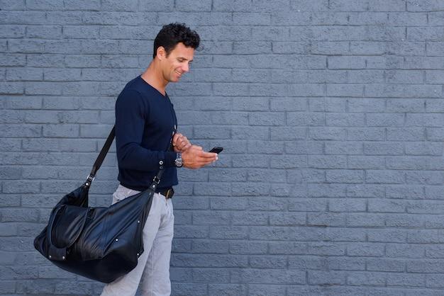 Bel homme voyageant avec sac et téléphone portable