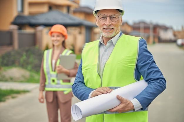 Un bel ingénieur civil souriant et une dame blonde derrière lui debout sur un chantier de construction