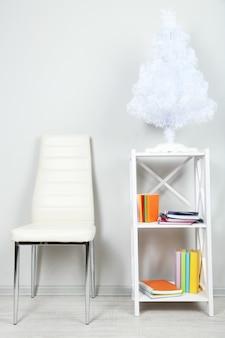 Bel intérieur avec chaise de couleur moderne, livres sur support en bois au mur