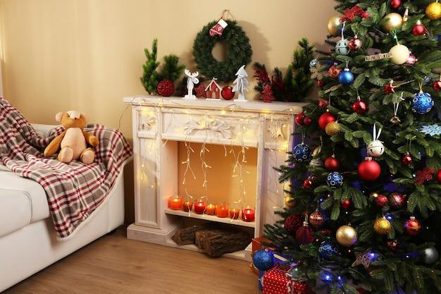 Bel intérieur de noël avec canapé, cheminée décorative et sapin