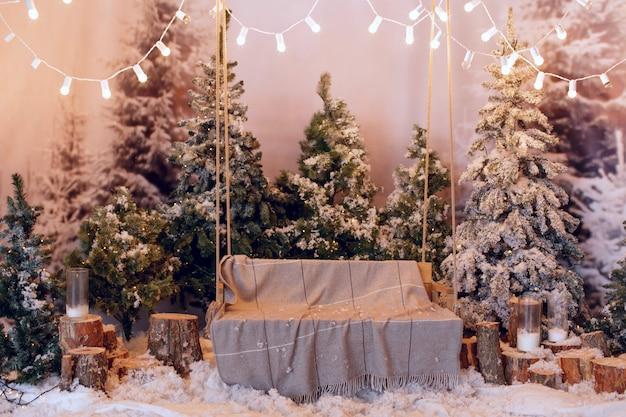 Bel intérieur de noël confortable avec des arbres enneigés et un banc.