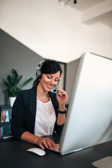 Bel opérateur féminin souriant parlant sur le casque avec le client.