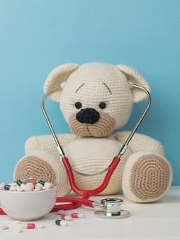 Un bel ours tricoté avec un stéthoscope et un grand nombre de médicaments.