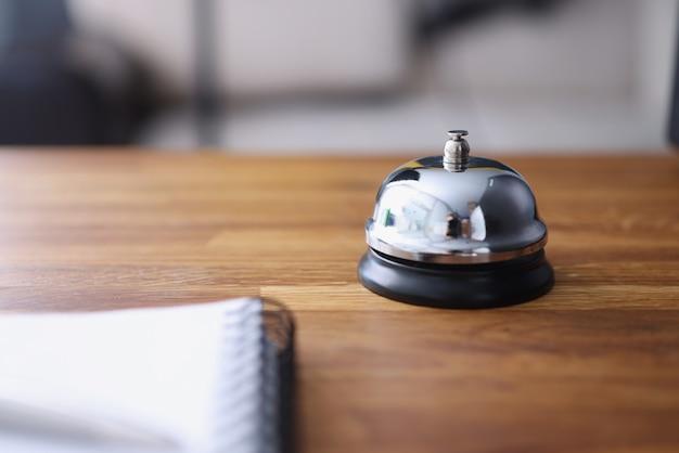 Bell se dresse sur un comptoir en bois pour attirer l'attention