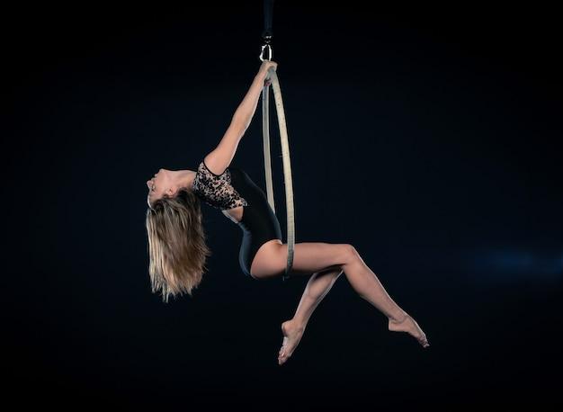 Belle acrobate aérienne féminine faisant des performances avec un cerceau aérien isolé sur fond noir.