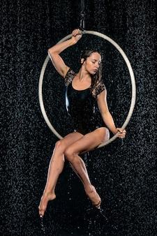 Belle acrobate féminine mince assis dans un cerceau aérien sous la pluie sur fond noir.