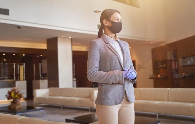 Belle administratrice caucasienne portant des gants en caoutchouc et un masque en tissu regardant au loin dans le hall