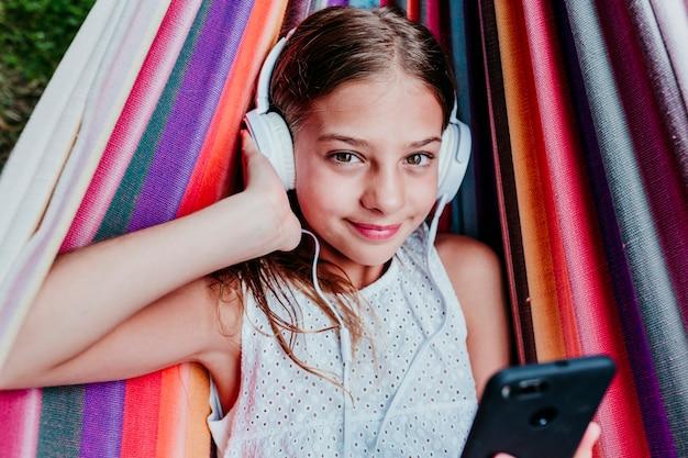 Belle adolescente allongée sur un hamac coloré dans le jardin. écouter de la musique sur un téléphone portable et un casque et sourire
