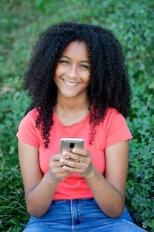 Belle adolescente américaine afro avec son smartphone