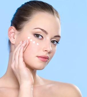 Belle adolescente appliquant une crème cosmétique sur la peau autour des yeux