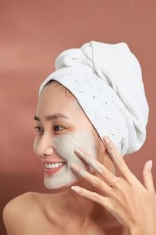 Belle adolescente asiatique joyeuse appliquant un masque facial à l'argile. soins de beauté, isolés sur fond clair.