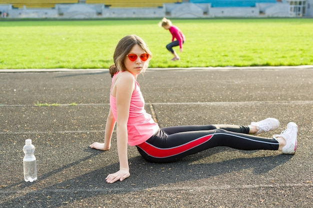 Belle adolescente au repos après une séance d'entraînement au stade