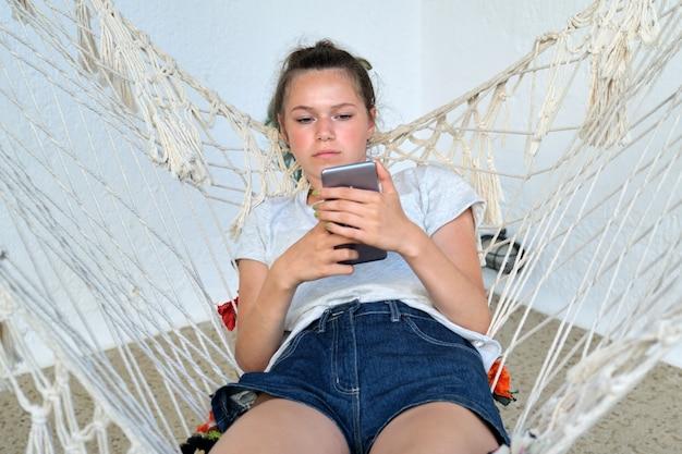 Belle adolescente au repos dans un hamac avec smartphone. mode de vie, loisirs, loisirs, ados, jeunesse