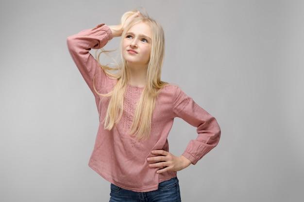 Belle adolescente aux cheveux longs blancs. un adolescent se tient et tient ses cheveux avec sa main
