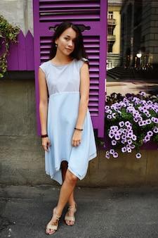 Belle adolescente en blouse bleue, contre une fenêtre en bois violette avec des fleurs.