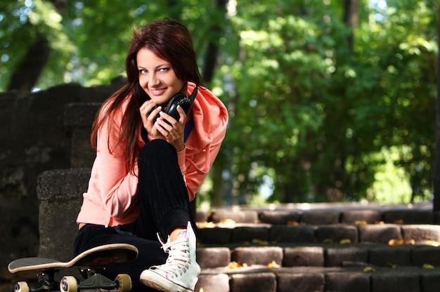 Belle adolescente avec un casque dans le parc