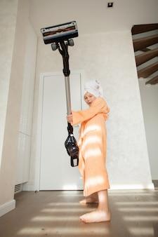 Belle adolescente dans un peignoir fait le ménage avec un aspirateur