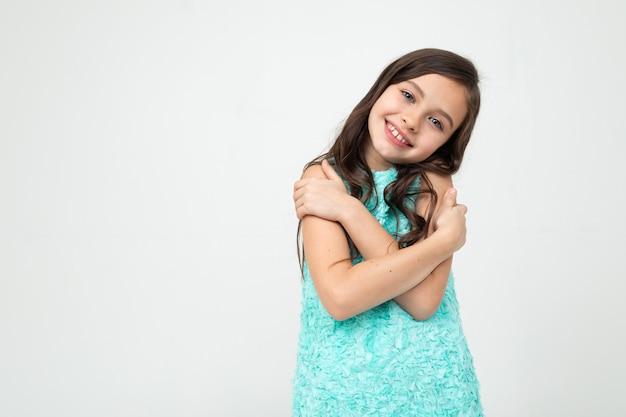 Belle adolescente dans une robe bleue s'embrasse sur un fond de studio blanc avec espace copie