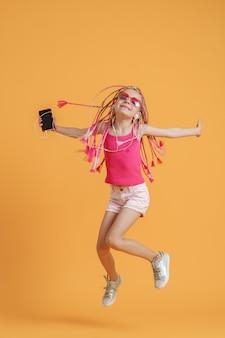 Belle adolescente avec des dreadlocks sautant avec un téléphone portable dans la main et écouter de la musique sur des écouteurs