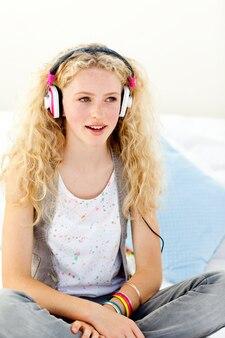 Belle adolescente écoutant de la musique sur son lit