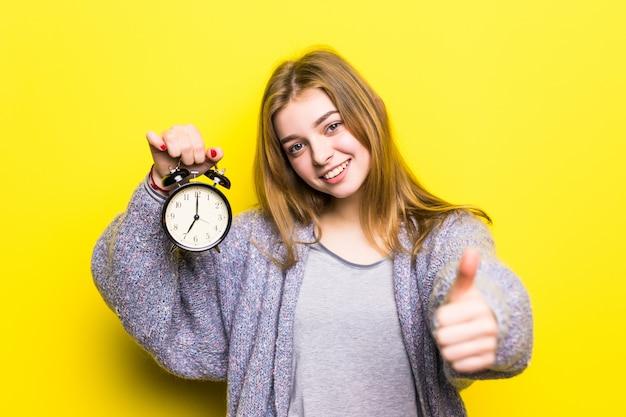 Belle adolescente étudiante avec réveil avec les pouces vers le haut, isolé