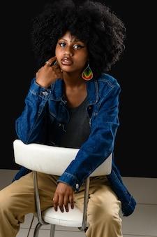 Belle adolescente avec de grands cheveux afro portant une veste jaens assise sur une dadeira