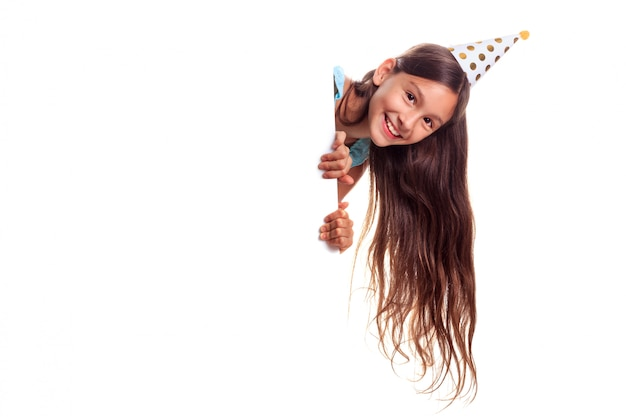 Belle adolescente heureuse avec des cheveux longs portant un chapeau de papier festif à la recherche de panneau d'affichage avec copie espace