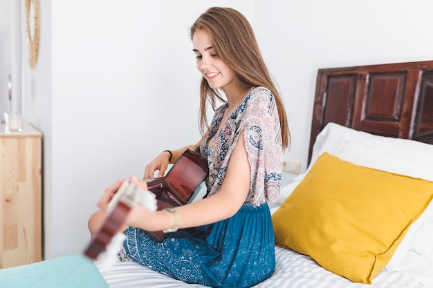 Belle adolescente jouant de la guitare dans la chambre