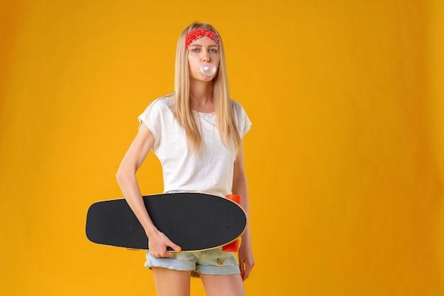 Belle et adolescente de mode posant avec une planche à roulettes en studio