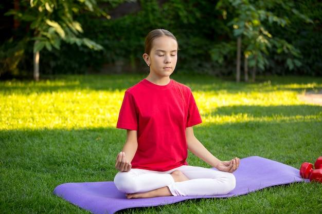 Belle adolescente pratiquant le yoga sur l'herbe au parc