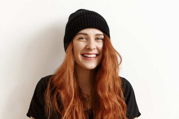 Belle adolescente rousse avec une coiffure en désordre regardant et souriant à la caméra