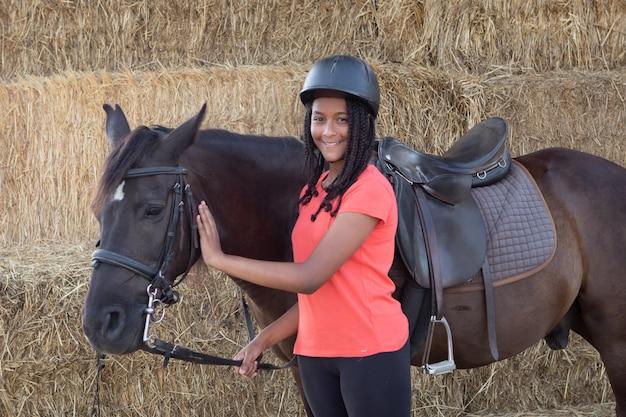 Belle adolescente avec son cheval qui apprend à monter