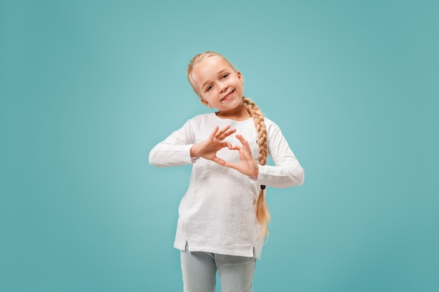 Belle adolescente souriante fait la forme d'un cœur avec ses mains sur le bleu