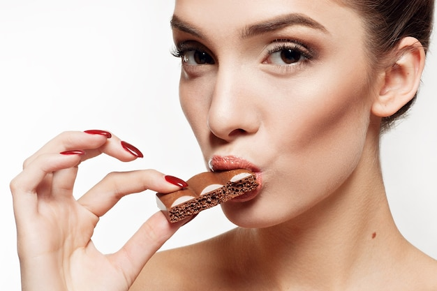Belle adolescente souriante, manger du chocolat