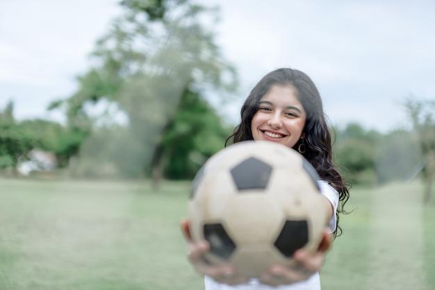 Belle adolescente tenant un ballon de soccer et floue fond de nature verdoyante