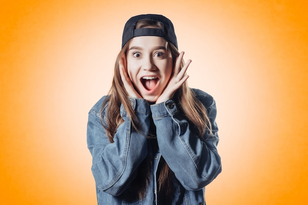 Belle adolescente en veste en jean sur une surface orange fait un visage wow surpris