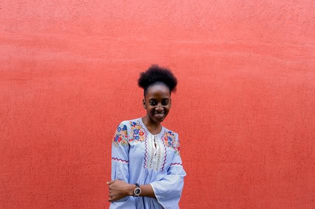 La belle afro-américaine contre le mur rouge