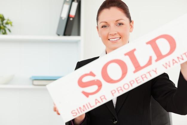 Belle agent immobilier tenant une pancarte vendue
