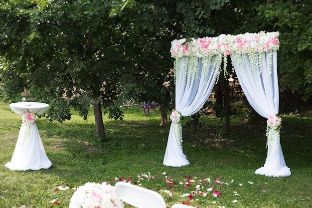 Belle arche blanche avec des décorations florales pour la cérémonie de mariage avec des chaises pour les invités sur fond vert avec des arbres