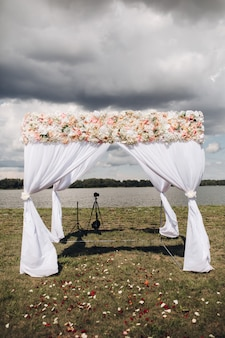 Belle arche de mariage avec des fleurs vue sur l'arche de mariage blanche avec des fleurs sur le dessus et des pétales de rose éparpillés sur l'herbe situé au bord de la rivière par temps nuageux
