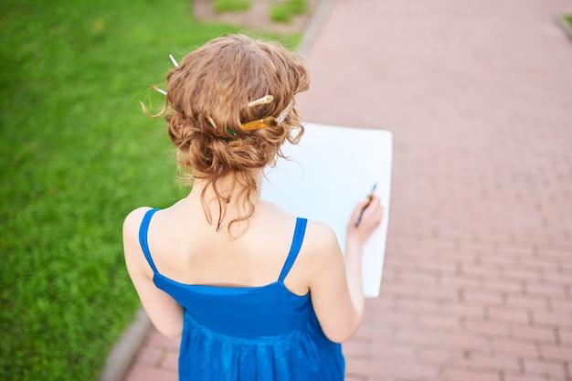 Une belle artiste dans la rue en robe bleue dessine un croquis de la photo