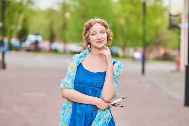 Belle artiste dans la rue en robe bleue souriante avec des glands dans les mains