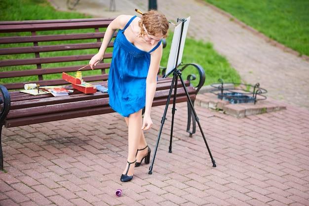 Une belle artiste dans la rue vêtue d'une robe bleue soulève la peinture tombée