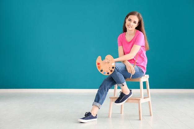 Belle artiste féminine assise sur un tabouret contre un mur de couleur